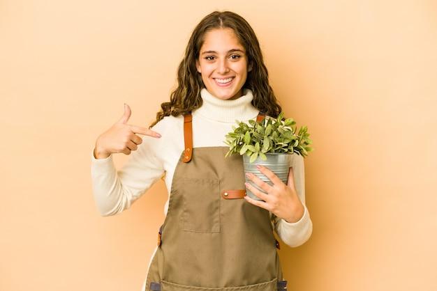 Młoda kobieta ogrodnik kaukaski gospodarstwa roślin na białym tle osoba, wskazując ręką na przestrzeni kopii koszuli, dumny i pewny siebie