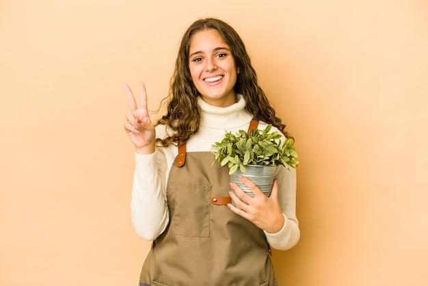 Młoda kobieta ogrodnik kaukaski gospodarstwa roślin na białym tle wyświetlono numer dwa palcami.