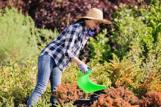 Młoda kobieta ogrodnik podlewania roślin w ogrodzie.