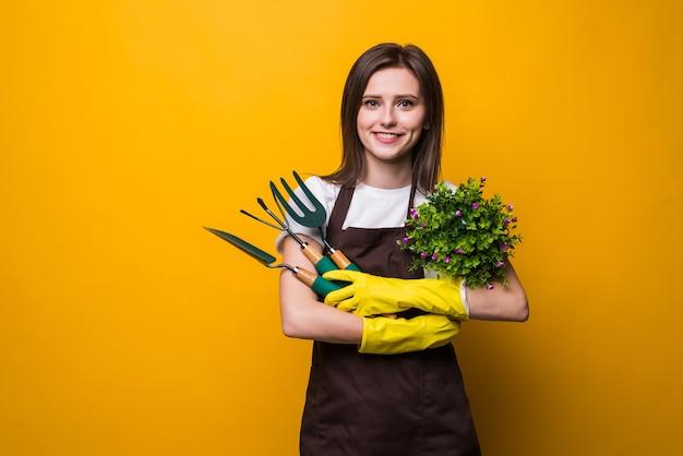 Młoda kobieta ogrodnik trzyma roślinę i narzędzia