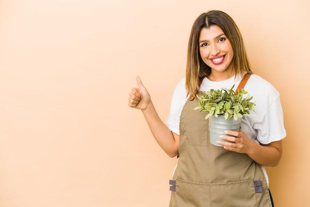 Młoda kobieta ogrodnik trzyma roślinę na białym tle uśmiechając się i podnosząc kciuk do góry