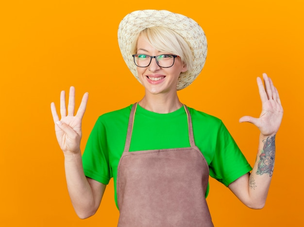 Młoda kobieta ogrodnik z krótkimi włosami w fartuch i kapelusz pokazuje i wskazuje palcami w górę numer dziewięć uśmiechnięty stojący na pomarańczowym tle