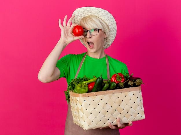 Młoda kobieta ogrodnik z krótkimi włosami w fartuch i kapelusz, trzymając skrzynię pełną warzyw