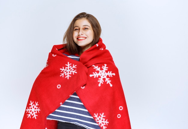Młoda kobieta okrywająca się czerwonym ciepłym kocem i trzymająca koc w niebieskie paski.