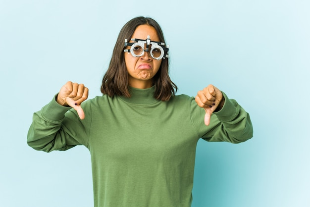 Młoda kobieta okulista na odizolowanej ścianie pokazuje kciuk w dół, pojęcie rozczarowania