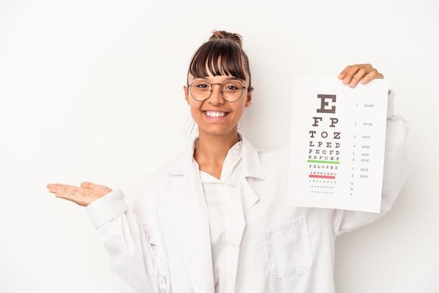 Młoda kobieta okulista rasy mieszanej robi test na białym tle pokazujący miejsce kopii na dłoni i trzymający drugą rękę na pasie.