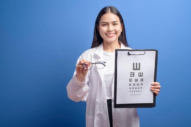Młoda kobieta okulista w okularach trzymając wykres oka na niebieskiej ścianie, koncepcja opieki zdrowotnej