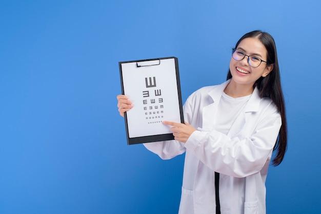 Młoda kobieta okulista w okularach trzymając wykres oka na niebiesko, koncepcja opieki zdrowotnej