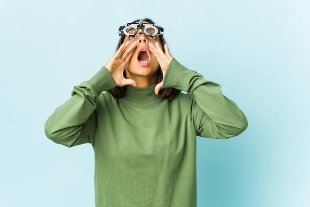 Młoda kobieta okulistka na odizolowanej ścianie krzyczy podekscytowany do przodu