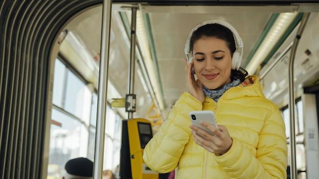 Młoda kobieta ono uśmiecha się podczas gdy stojący w pociągu, tramwaju lub autobusie. szczęśliwy żeński pasażer słucha muzyka na smartphone transporcie publicznie.