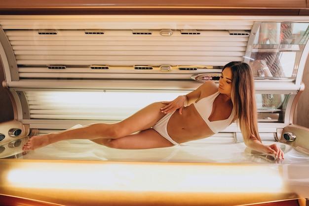 Młoda kobieta opala się w solarium