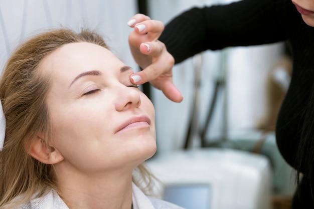 Młoda kobieta opiekować się twarzą w salonie piękności. zbliżenie.