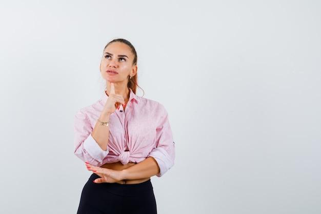 Młoda kobieta opierając brodę na palcu w koszuli i patrząc zamyślony, widok z przodu.