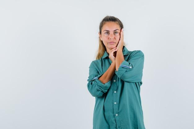 Młoda kobieta, opierając dłoń na policzku w zielonej bluzce i patrząc poważnie