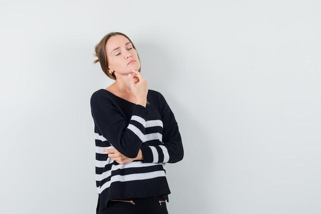 Młoda kobieta opierając podbródek na dłoni i stojąc w myślącej pozie w pasiastej dzianinie i czarnych spodniach, wyglądając zamyślony