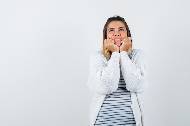 Młoda kobieta opierając podbródek na dłoniach w t-shirt, sweter i patrząc z nadzieją, widok z przodu.