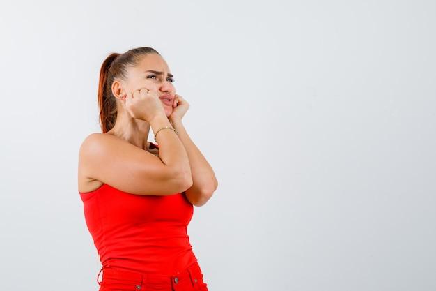 Młoda kobieta opierając podbródek na rękach w czerwonym podkoszulku bez rękawów, spodniach i słodko wyglądającym. przedni widok.