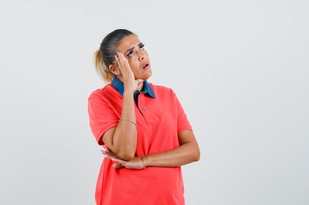 Młoda kobieta, opierając policzek na dłoni, myśląc o czymś w czerwonej koszulce i patrząc zamyślony, widok z przodu.