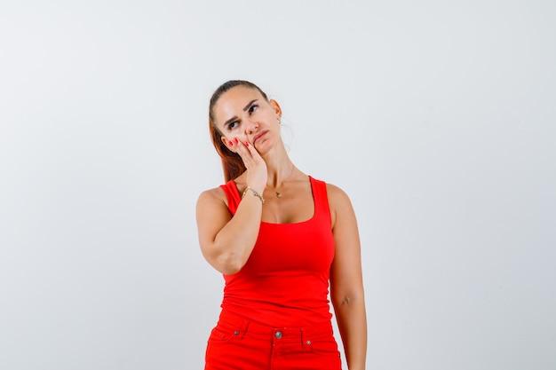 Młoda kobieta opierając policzek na dłoni w czerwonym podkoszulku, spodniach i patrząc zamyślony, widok z przodu.
