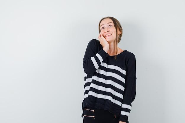 Młoda kobieta opierając policzek na dłoni w dzianinie w paski i czarnych spodniach i wyglądająca na szczęśliwą