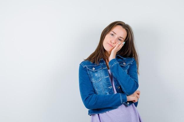 Młoda kobieta opierając policzek na dłoni w koszulce, kurtce i patrząc na zmęczoną, widok z przodu.