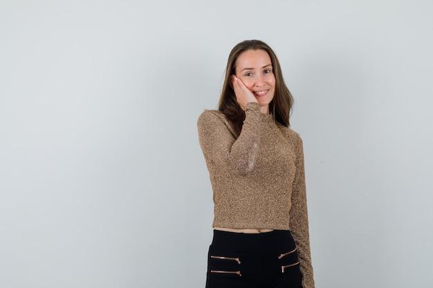 Młoda kobieta opierając policzek na dłoni w pozłacanym swetrze i czarnych spodniach i wyglądająca na szczęśliwą