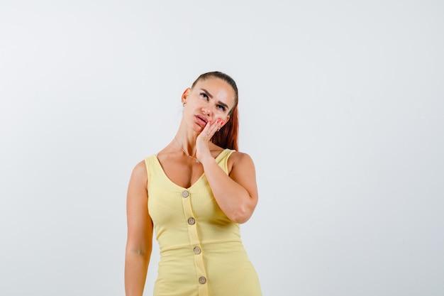 Młoda kobieta, opierając policzek pod ręką, patrząc w żółtą sukienkę i patrząc zamyślony