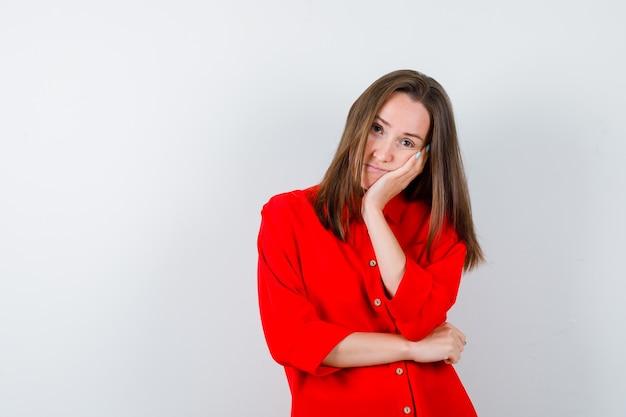 Młoda kobieta opierając policzek pod ręką w czerwonej bluzce i patrząc zamyślony. przedni widok.