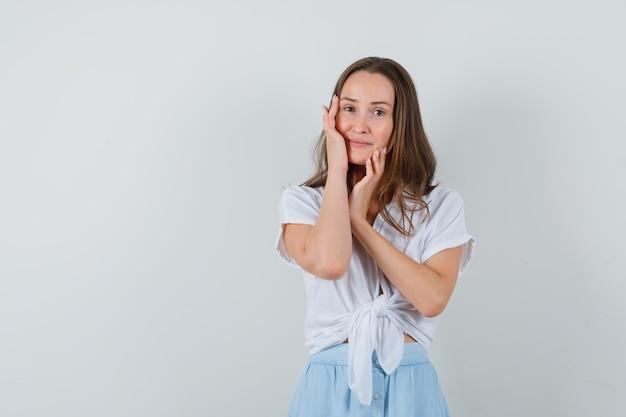 Młoda kobieta opierając policzki na dłoni w białej bluzce i jasnoniebieskiej spódnicy i wygląda elegancko