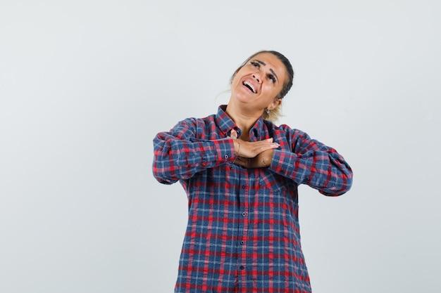 Młoda kobieta, opierając ręce na piersi w kraciastej koszuli i zamyślony patrząc. przedni widok.