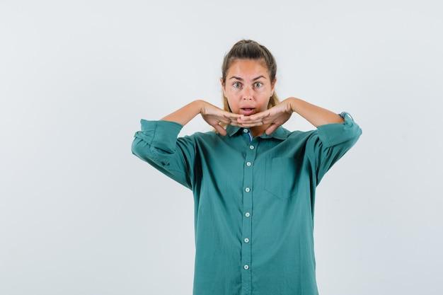 Młoda kobieta, opierając się na jej połączonych rękach w niebieskiej koszuli i wyglądająca na zaskoczoną