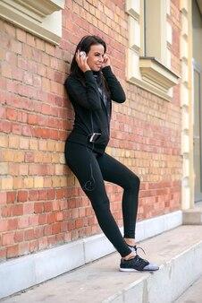 Młoda kobieta, opierając się na mur z cegły