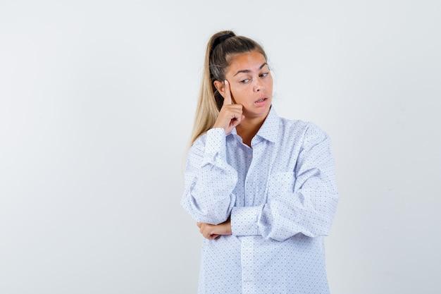 Młoda kobieta opierająca policzek na palcu wskazującym, myśląca o czymś w białej koszuli i zamyślona