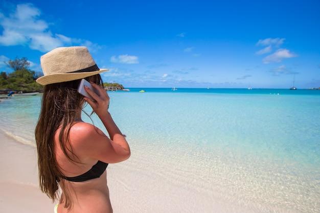 Młoda kobieta opowiada na jej telefonie przy tropikalną plażą
