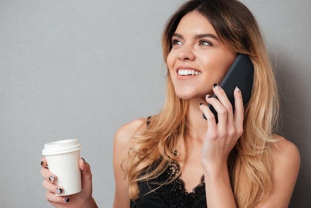 Młoda kobieta opowiada na telefonie komórkowym podczas gdy trzymający filiżankę