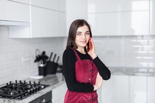Młoda kobieta opowiada na telefonie komórkowym podczas gdy używać laptop w kuchni w domu