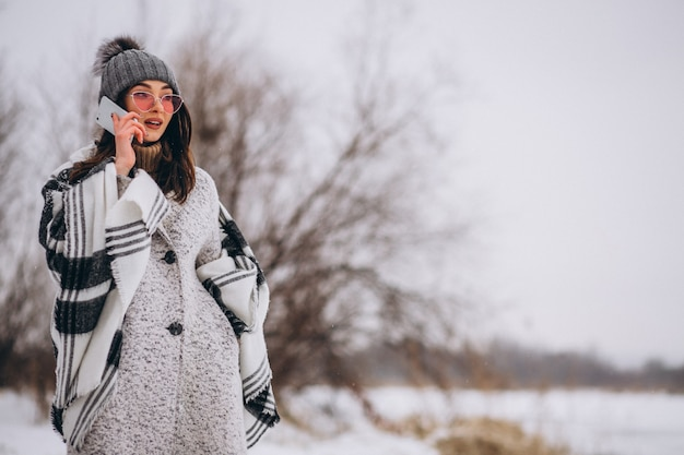 Młoda kobieta opowiada na telefonie outside w zima parku