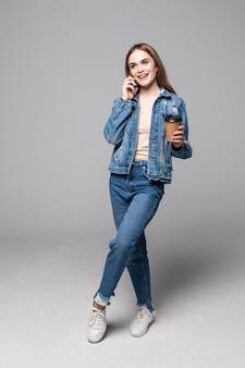 Młoda kobieta opowiada telefonem komórkowym pije kawowy pozować odizolowywam nad szarości ścianą