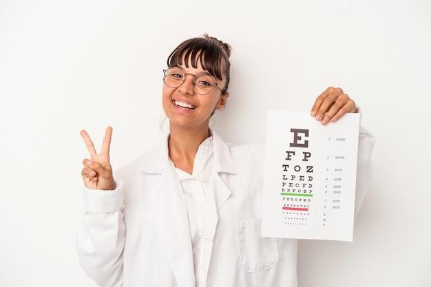 Młoda kobieta optyk rasy mieszanej robi test na białym tle radosny i beztroski pokazując symbol pokoju palcami.