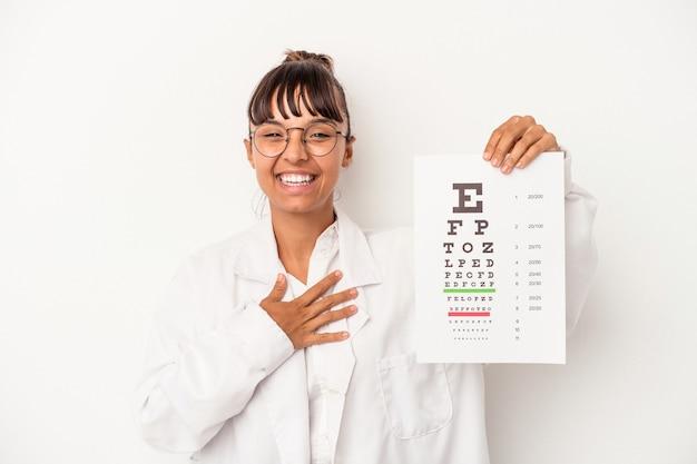 Młoda kobieta optyk rasy mieszanej robi test na białym tle śmieje się głośno trzymając rękę na klatce piersiowej.
