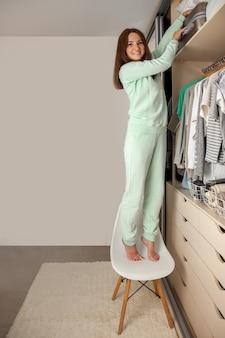 Młoda kobieta organizuje przechowywanie na górnej półce w szafie. walizka i poduszki na antresoli. przechowywanie ubrań.