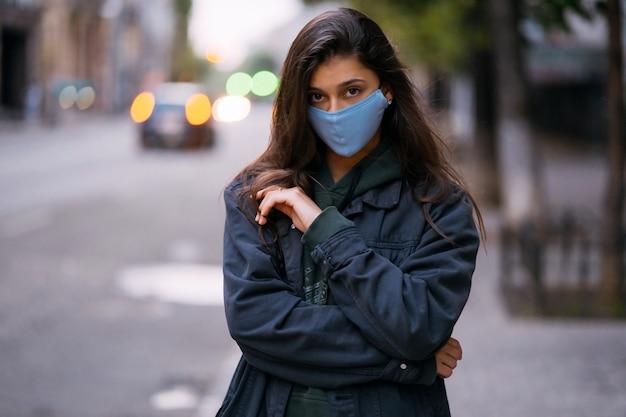 Młoda kobieta, osoba w ochronnej sterylnej masce medycznej przy pustej ulicy