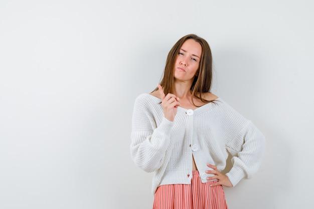 Młoda kobieta ostrzeżenie z palcem w swetrze i spódnicy patrząc złośliwie na białym tle