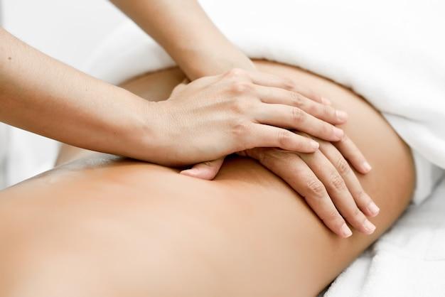 Młoda kobieta otrzymania masaż kręgosłupa w centrum spa.
