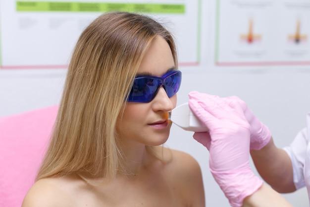 Młoda kobieta otrzymująca leczenie laserowe. pojęcie zdrowia i urody.
