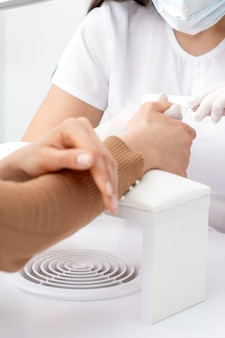 Młoda kobieta otrzymująca manicure pilnikiem do paznokci