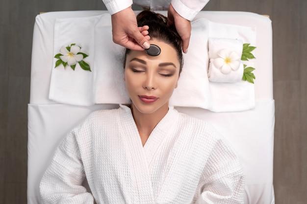 Młoda kobieta otrzymująca masaż twarzy kamieniem mineralnym