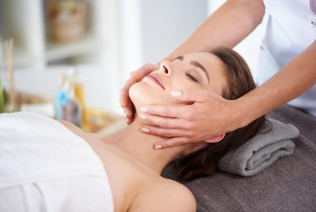 Młoda kobieta otrzymująca profesjonalny masaż twarzy