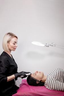 Młoda kobieta otrzymująca ultradźwiękowy peeling kawitacyjny do oczyszczania twarzy. kosmetologia zabieg do pielęgnacji skóry twarzy czyszczenie