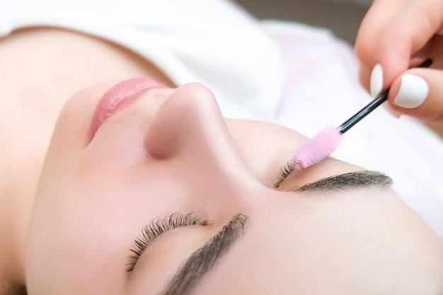 Młoda kobieta otrzymująca zabieg laminowania rzęs w salonie kosmetycznym, z bliska
